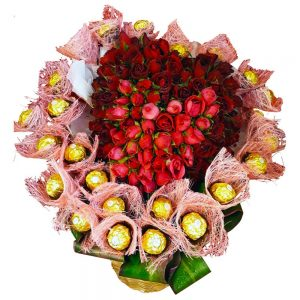 A basket of Red Roses in the shape of a heart surrounded by Chocolates