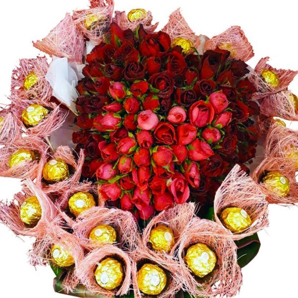 A basket of Red Roses in the shape of a heart surrounded by Chocolates, close up